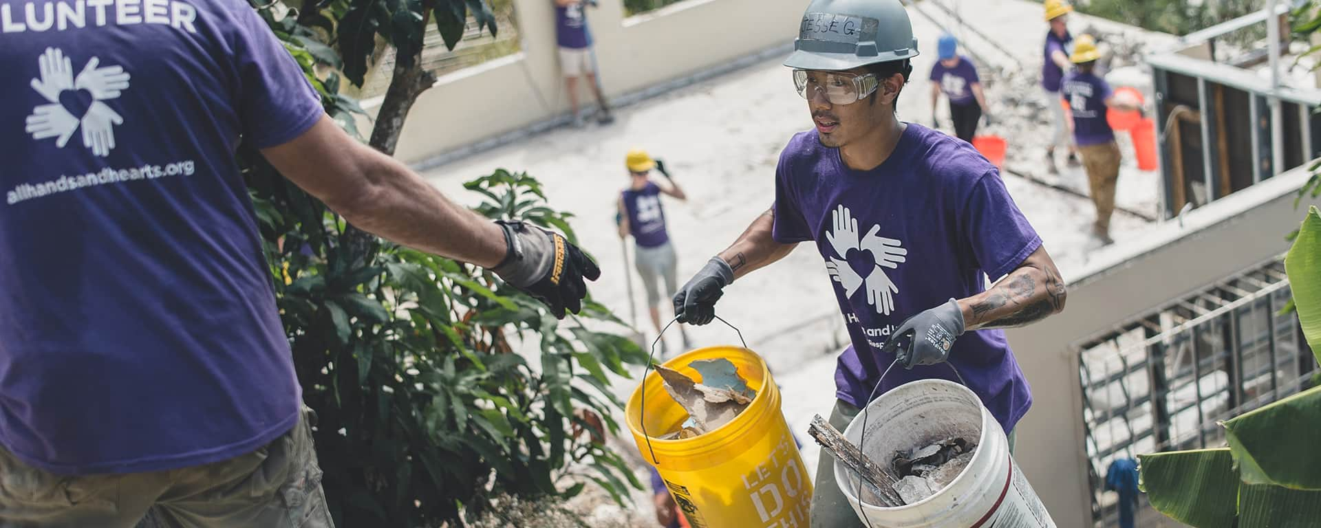 An international volunteer carrying and passing buckets of debris