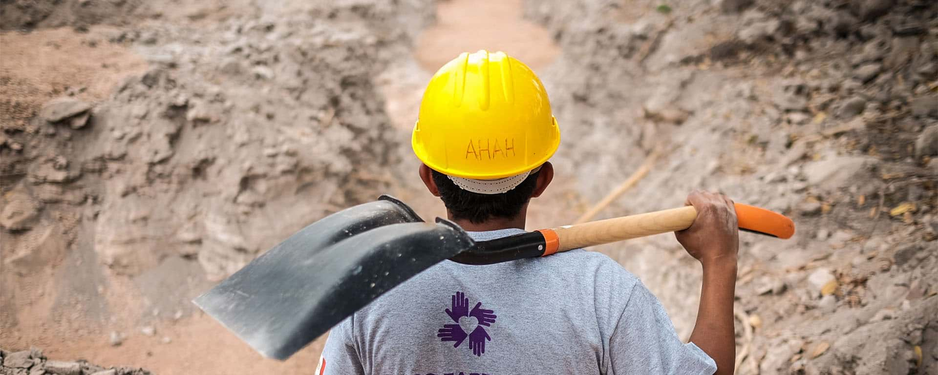 International volunteer holding a spade and overlooking the post-disaster site in Mexico